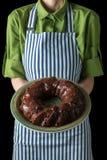 Il cuoco unico in un grembiule che tiene un bigné ha piovigginato con cioccolato su un piatto verde Priorità bassa nera Fotografia Stock Libera da Diritti