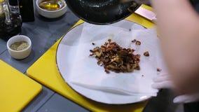 Il cuoco unico versa i funghi su un piatto video d archivio