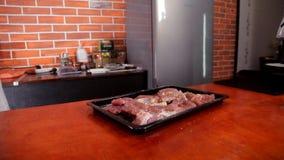 Il cuoco unico versa la carne con il succo di limone e pone foglio di cottura nel forno stock footage