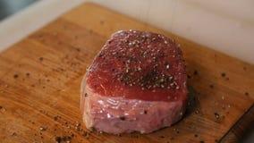 Il cuoco versa fuori la bistecca di manzo delle lastre di vetro del pepe nero archivi video