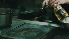 Il cuoco versa l'olio nel primo piano della pentola archivi video