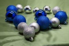 Il cuore è allineato con le palle di Natale su fondo verde Fotografia Stock