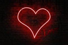 Il cuore al neon rosso ha modellato il segno su un muro di mattoni immagine stock libera da diritti
