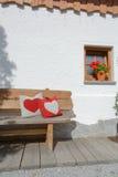 Il cuore appoggia su un banco del giardino con i fiori Immagini Stock Libere da Diritti