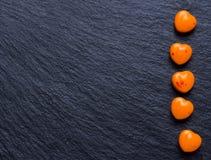 Il cuore arancio ha modellato le pillole o la caramella sul nero di lerciume Fotografia Stock