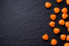 Il cuore arancio ha modellato le pillole o la caramella sul nero di lerciume Fotografie Stock