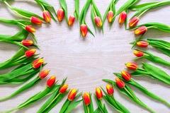 Il cuore dai tulipani rossi fiorisce sulla tavola rustica per il giorno dell'8 marzo, di Giornata internazionale della donna, di  Immagine Stock