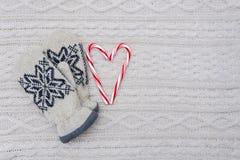 Il cuore dei bastoncini di zucchero e dei guanti su bianco ha tricottato il fondo Fotografie Stock