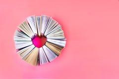 Il cuore dei libri su fondo di corallo Vista superiore Libri di storia di amore Copi lo spazio immagine stock