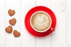 Il cuore del giorno di biglietti di S. Valentino ha modellato i biscotti e la tazza di caffè rossa Immagini Stock Libere da Diritti