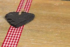 Cuore dell'ardesia su un pannello di legno. Fotografia Stock