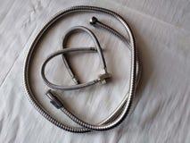 Il cuore dell'idraulico è fatto dei tubi flessibili dell'acqua per un lavandino, una treccia del metallo di colore d'acciaio, San immagine stock