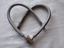 Il cuore dell'idraulico è fatto dei tubi flessibili dell'acqua per un lavandino, una treccia del metallo di colore d'acciaio, San immagini stock libere da diritti