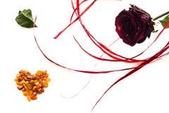 Il cuore della carta ambrata ed è aumentato per il San Valentino isolato su bianco Fotografia Stock