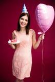 Il cuore della tenuta della donna ha modellato il pallone e la ciambella con la candela immagini stock libere da diritti