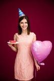 Il cuore della tenuta della donna ha modellato il pallone e la ciambella con la candela immagine stock libera da diritti