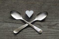 Il cuore dello zucchero bianco con due ha attraversato i cucchiai, concetto non sano Immagini Stock