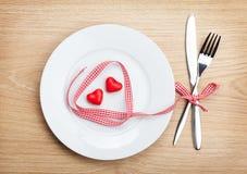 Il cuore di San Valentino ha modellato il nastro rosso sopra il piatto con il silverwa Immagine Stock