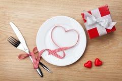 Il cuore di San Valentino ha modellato il nastro rosso sopra il piatto con il silverwa Immagini Stock Libere da Diritti