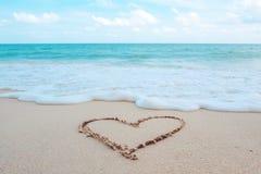Il cuore di scrittura della mano ha modellato sulla spiaggia dal mare con le onde ed il cielo blu bianchi Fotografie Stock