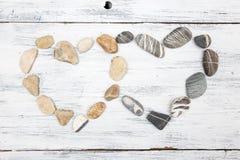 Il cuore due ha modellato le pietre del ciottolo su un vecchio legno Fotografia Stock