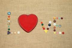 Il cuore e la parola rossi amano scrivere con i bottoni di cucito Fotografia Stock