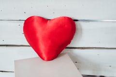 Il cuore ha modellato il cuscino su un fondo di legno bianco Fotografia Stock