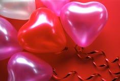 Il cuore ha modellato gli aerostati del partito su una priorità bassa rossa Fotografia Stock Libera da Diritti