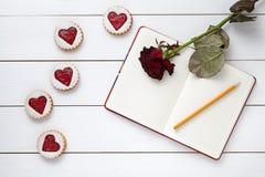 Il cuore ha modellato i biscotti con il taccuino vuoto, la matita ed il fiore rosa su fondo di legno bianco per il giorno di bigl Fotografie Stock