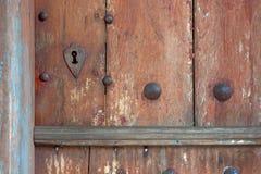 Il cuore ha modellato i bordi del buco della serratura in vecchia porta di legno Fotografia Stock