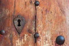 Il cuore ha modellato i bordi del buco della serratura in vecchia porta di legno Fotografia Stock Libera da Diritti