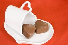 Il cuore ha modellato il cioccolato e la tazza su priorità bassa rossa Fotografia Stock Libera da Diritti