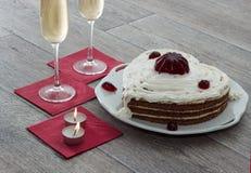 Il cuore ha modellato il dolce con marmellata d'arance rossa, due vetri di champagne e due candele servite sui tovaglioli contro  Fotografia Stock