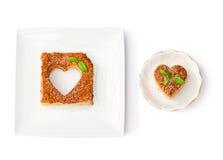 Il cuore ha modellato il dolce di millefoglie con la menta sui piatti bianchi isolati fotografie stock