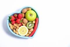 Il cuore ha modellato il piatto con le verdure isolate su fondo di legno Immagine Stock