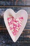 Il cuore ha modellato la ciotola con gli zuccheri canditi rosa e bianchi per il valentin Immagine Stock