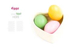 Il cuore ha modellato la scatola in pieno di uova di Pasqua Variopinte su bianco Immagine Stock