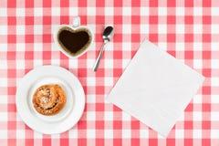 Il cuore ha modellato la tazza di caffè e un rotolo di cannella Fotografie Stock