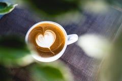 Il cuore ha modellato il latte del caffè sulla tavola di legno immagine stock