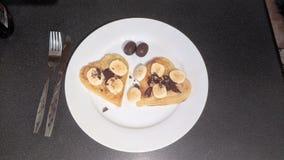 Il cuore ha modellato il pancake con cioccolato e le banane e le uova di cioccolato Fotografie Stock