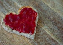 Il cuore ha modellato il pane tostato con inceppamento immagine stock