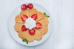 Il cuore norvegese ha modellato le cialde completate con le fragole, menta ed ha montato la crema sul piatto bianco e sul fondo d Fotografie Stock Libere da Diritti