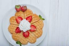 Il cuore norvegese ha modellato le cialde completate con le fragole, menta ed ha montato la crema sul piatto bianco e sul fondo d Immagini Stock