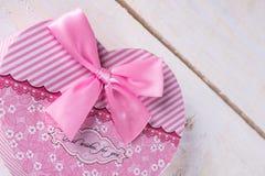 Il cuore rosa di colore ha modellato la scatola con l'arco rosa sopra fondo di legno Immagine Stock Libera da Diritti