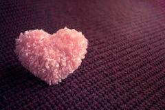 Il cuore rosa lanuginoso del filo su buio ha tricottato il fondo di Borgogna Ha Fotografia Stock