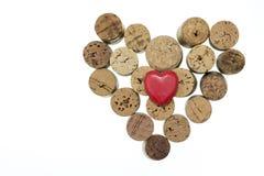 Il cuore rosso con vino tappa la forma una forma del cuore sullo spazio bianco isolato della copia del fondo Immagini Stock