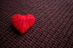 Il cuore rosso del filo su buio ha tricottato il fondo di Borgogna P fatta a mano fotografie stock
