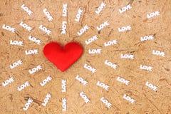 Il cuore rosso del tessuto è stato circondato vicino e logotypes di amore Immagini Stock Libere da Diritti