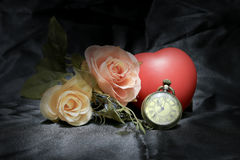 Il cuore rosso ed è aumentato con l'orologio da tasca d'annata dell'oro sul fondo nero del tessuto Amore del concetto di tempo St Fotografie Stock