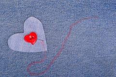 Il cuore rosso ha modellato il bottone con l'ago ed il filo rosso fotografia stock libera da diritti